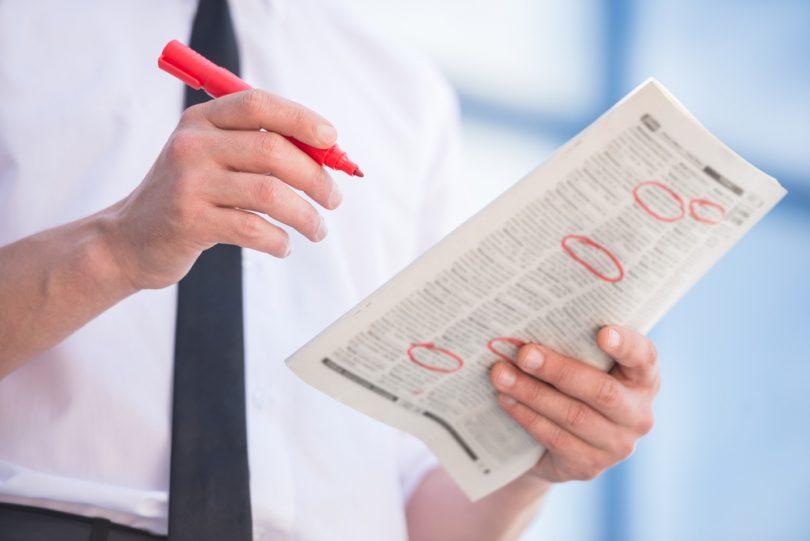 homme cherchant un emploi dans le journal