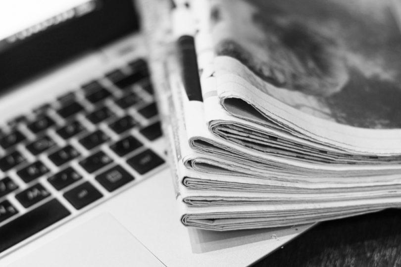 journaux posés sur un ordinateur portable sur un fond noir et blanc