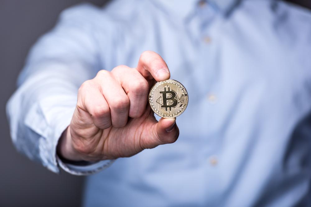 homme qui tient un token de Bitcoin entre ses mains