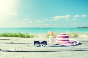 lunette de soleil avec une lotion et un chapeau