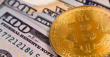 une pièce de bitcoin posée sur des dollars